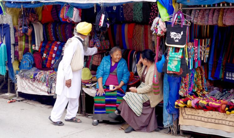 a Sikh Indian man buying souvenirs from Tibetan ladies in Jogiwara Road, McLeod Ganj, India